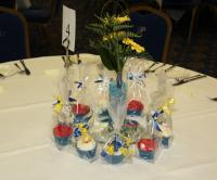 A beautiful floral arrangement and an array of delicous cup cakes